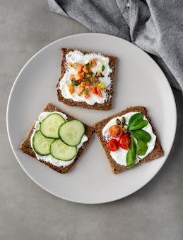 Pane tostato sano della colazione con le fette di cetriolo sulla zolla