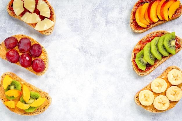Sana colazione brindisi con burro di arachidi, marmellata di fragole, banana, uva, pesca, kiwi, ananas, noci. copia spazio