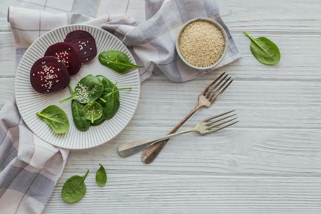Prima colazione sana con foglie di spinaci bollite barbabietola e semi di sesamo sulla tavola di legno bianca
