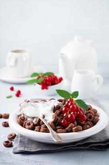 Sana colazione con anelli di mais al cioccolato, bacche di ribes rosso, yogurt e tè su uno sfondo grigio cemento copia spazio.