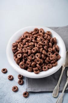 Sana colazione con anelli di mais al cioccolato, bacche di ribes rosso, yogurt e tè su uno sfondo grigio cemento