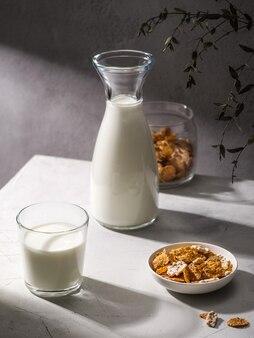Sana colazione con cornflakes e latte. bicchiere di latte e ciotola con gustosi cornflakes su sfondo grigio. luce dura, ombra.