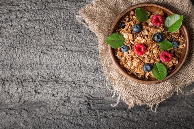 Sana colazione con muesli e frutti di bosco su sfondo scuro. Foto Premium