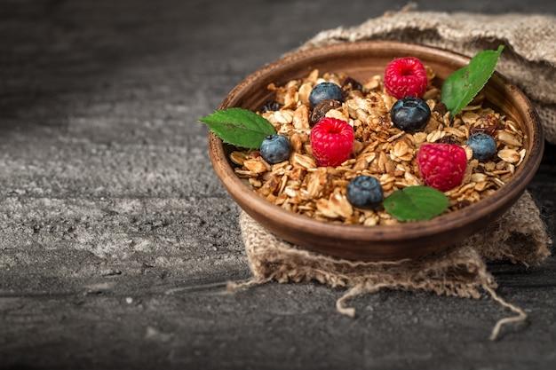 Sana colazione con muesli e frutti di bosco su sfondo scuro.