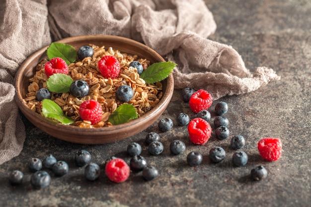 Sana colazione con muesli e frutti di bosco su sfondo scuro