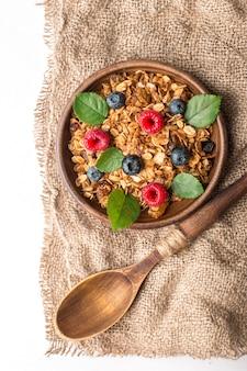 Prima colazione sana con granola e le bacche su fondo bianco. Foto Premium