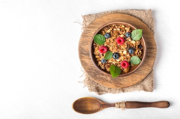 Sana colazione con muesli e frutti di bosco su sfondo bianco