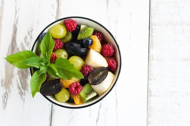 Prima colazione sana con un mix di frutta e bacche in una ciotola su un tavolo bianco. concetto di perdita di peso. vista dall'alto.