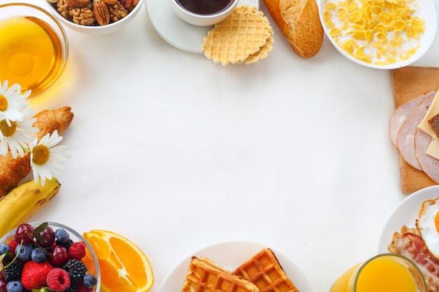 Prima colazione sana con muesli, frutta, bacche, noci, caffè, uova, miele su fondo bianco