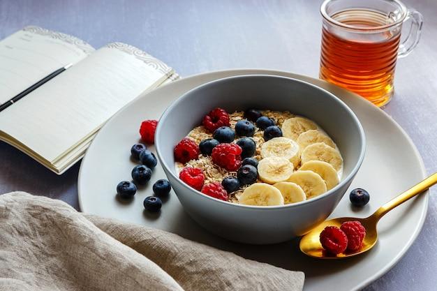 Sana colazione con farina d'avena in una ciotola, fette di banana, lampone, mirtillo, una tazza di tè e un taccuino con una penna sul piano del tavolo grigio chiaro