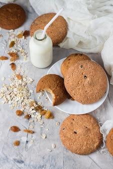 Sana colazione con biscotti di farina d'avena, uvetta, farina d'avena e latte su uno sfondo chiaro. concetto di alimentazione sana