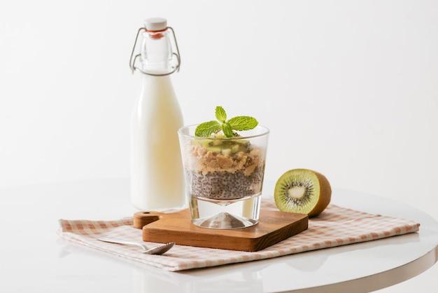 Sana colazione con yogurt, noci, kiwi e semi di chia. ciotola di frutta fresca.