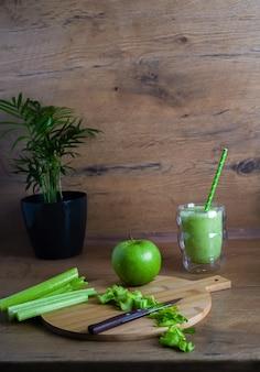 Sana colazione su un tavolo di legno, mela verde e sedano tritato e un bicchiere di succo o frullato per uno stile di vita sano e una perdita di peso. foto di alta qualità.