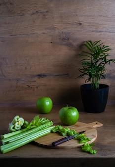 Sana colazione su un tavolo di legno, mela verde e sedano tritato per uno stile di vita sano e una perdita di peso. foto di alta qualità
