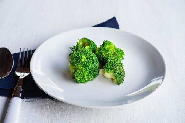 Broccoli sani in un piatto sulla tavola di legno bianca
