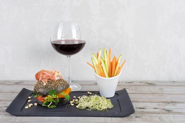 Hamburger sano con hamon, pomodori, micro verdure e panini integrali neri, bastoncini di verdure e vino rosso su lavagna nera