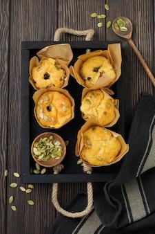 Muffin al formaggio sani con polenta, pomodorini e semi di zucca per colazione. messa a fuoco selettiva. vista dall'alto. copia spazio. Foto Premium