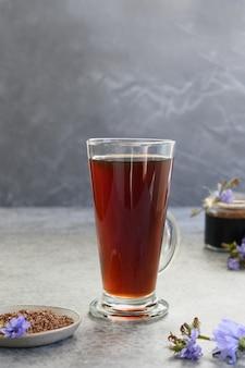 Bevanda sana di cicoria come caffè in vetro e fiori blu freschi d'estate. istantaneo e concentrato. verticale. avvicinamento.