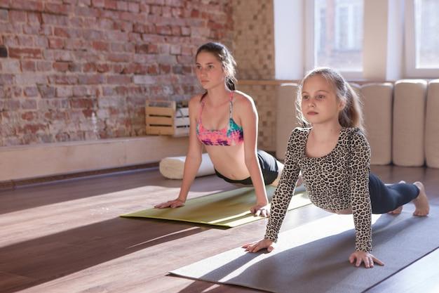 Stile di vita sano dei bambini. yoga per bambini. sviluppo della ginnastica, sport adolescenziale. giovani ragazze in studio, sfondo palestra, concetto di salute
