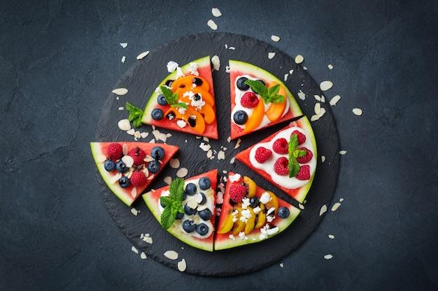 Mangiare sano e pulito, dieta e nutrizione, stagionale, concetto estivo. pizza all'anguria con frutti di bosco, frutta, yogurt, formaggio feta su un tavolo. vista dall'alto piatto laici copia spazio sfondo.