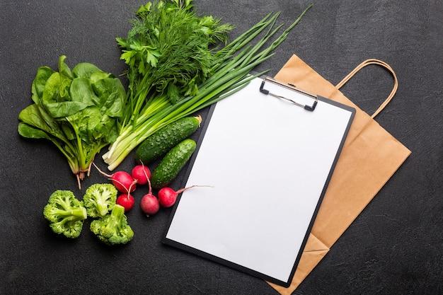 Cibo sano e pulito per vegetariani sacco di carta e vista dall'alto di un quaderno bianco su sfondo nero