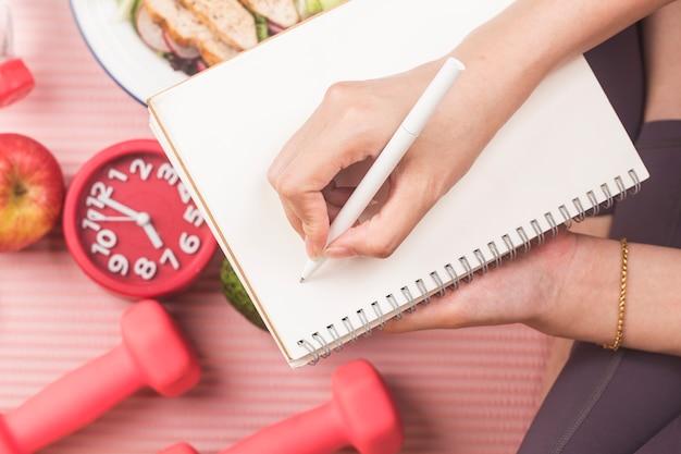 Concetto sano con cibo nutrizionale nella scatola del pranzo e attrezzature per il fitness con la donna che scrive il tempo per rimanere in buona salute sul libro del diario