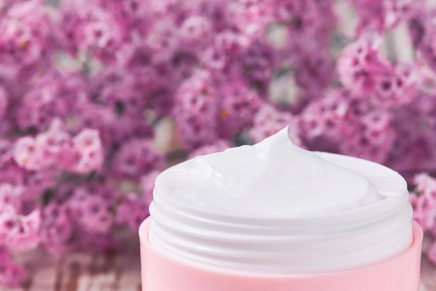 Crema cosmetica sana con cura del viso a base di erbe o lozione idratante, primo piano. vaso di plastica rosa per crema per la pelle sensibile su un tavolo di legno.