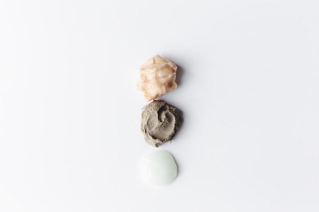 Concetto di cosmetici sani con texture cosmetiche e macchie di scrub corpo diverso sul tavolo bianco. scrub corpo all'argilla, riso e mandorle