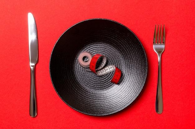 Concetto di dieta sana del piatto con metro a nastro, forchetta e coltello su sfondo rosso. vista dall'alto.