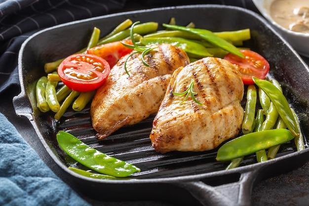 Dieta sana di pollo in padella con piselli e pomodori da vicino.