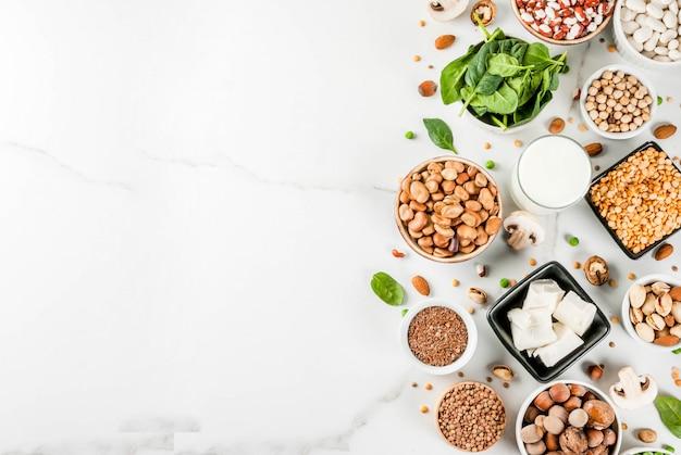 Alimenti vegani dietetici, fonti proteiche vegetali: tofu, latte vegano, fagioli, lenticchie, noci, latte di soia, spinaci e semi. vista dall'alto sul tavolo bianco.