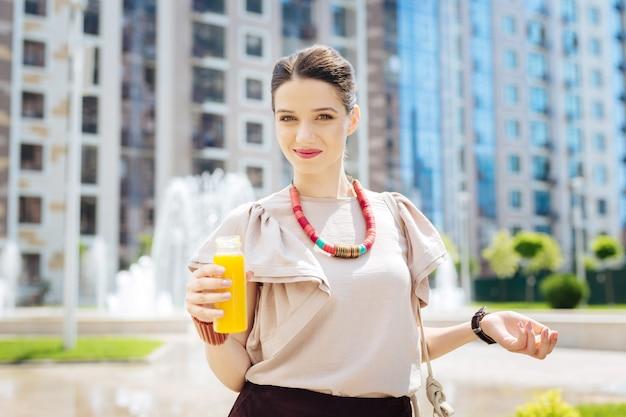Bevanda salutare. piacevole donna attraente sorridente mentre beve il succo d'arancia