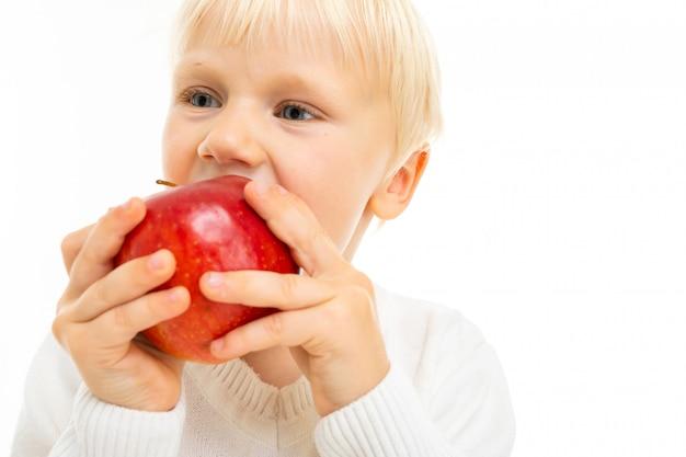 Concetto di mangiare sano. cool piano maschio figlio bambino morde una mela rossa matura su bianco con spazio di copia