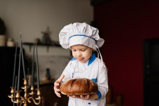 Concetto di mangiare sano. ragazzino felice sta cucinando in cucina in una soleggiata giornata estiva. il fornaio del bambino su un picnic mangia pane e bagel in un grembiule e un cappello bianchi