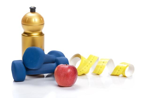 Alimentazione sana, dieta e perdita di peso, disintossicazione. manubri, mela e una bottiglia d'acqua