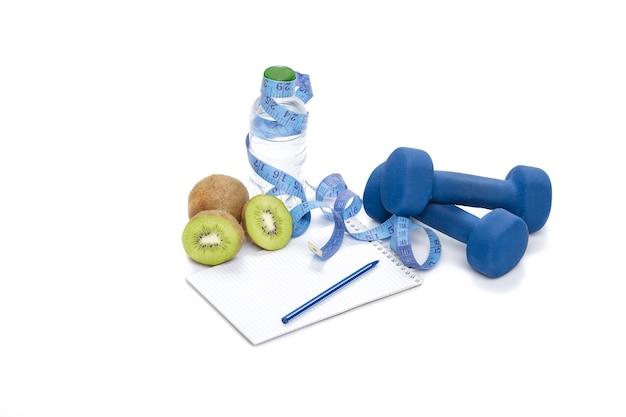 Alimentazione sana, dieta e perdita di peso, disintossicazione. manubri, kiwi e una bottiglia d'acqua