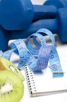 Alimentazione sana, dieta e perdita di peso, disintossicazione. manubri, kiwi e metro a nastro