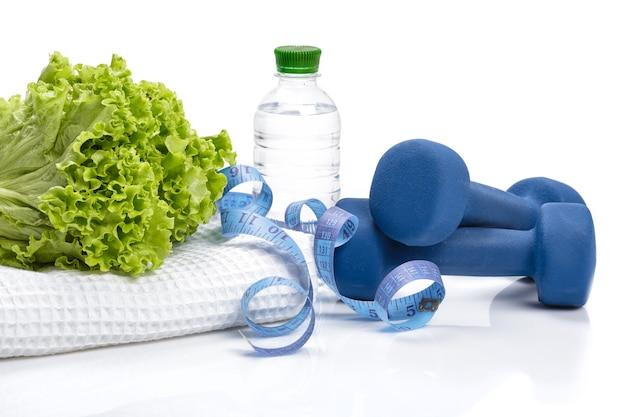 Alimentazione sana, dieta e perdita di peso, disintossicazione. manubri, lattuga e una bottiglia d'acqua