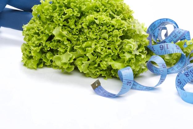 Alimentazione sana, dieta e perdita di peso, disintossicazione. manubri, lattuga e metro a nastro