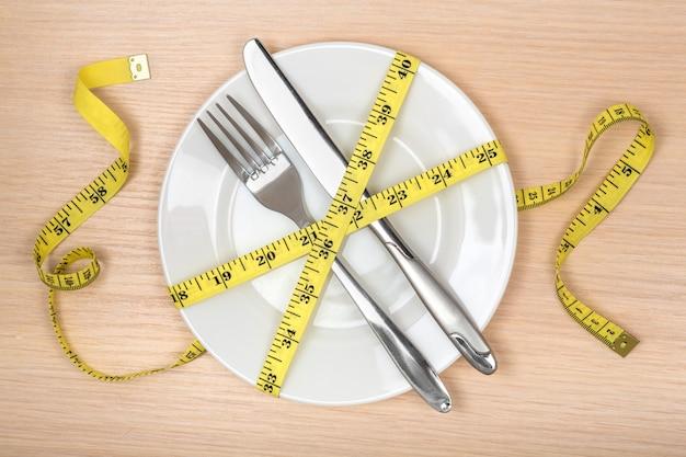 Mangiare sano o concetto di dieta. piatto vuoto, forchetta e coltello avvolti nel metro a nastro