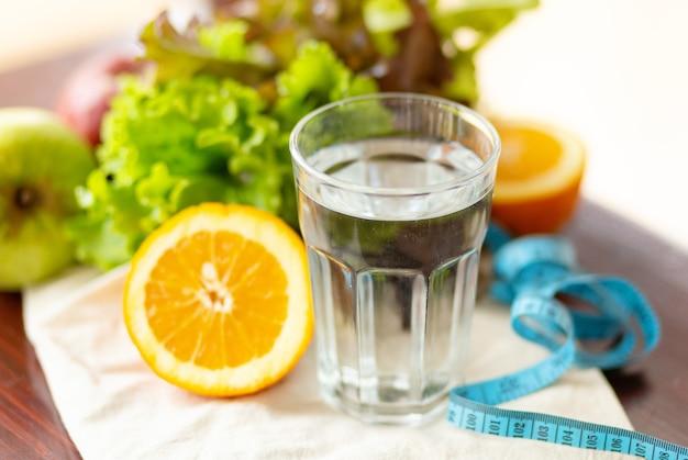 Mangiare sano, bevande, misurazione del nastro blu, dieta, disintossicazione e concetto di persone - chiudere l'acqua di frutta in vetro