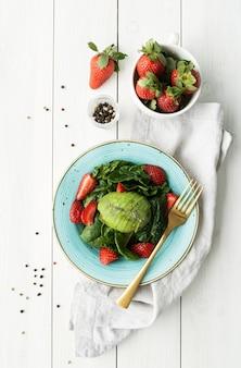 Mangiare sano. insalata con fragole, avocado, spinaci su un fondo di legno bianco vista dall'alto laici piatta