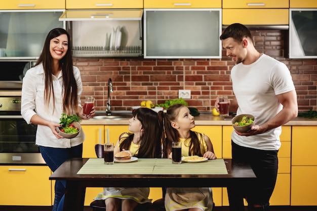 Alimentazione sana vs cattive abitudini. i genitori offrono alle loro figlie un'insalata con succo invece di un hamburger e una bibita. le bambine non sono felici. concetto di cibo spazzatura