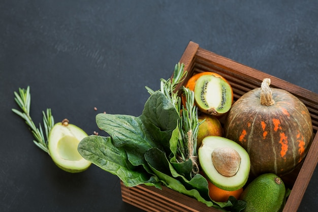 Alimento biologico sano dell'agricoltore in scatola di legno: frutta, verdura, semi, superfood, ortaggio a foglia su fondo nero. concetto di selezione del cibo pulito