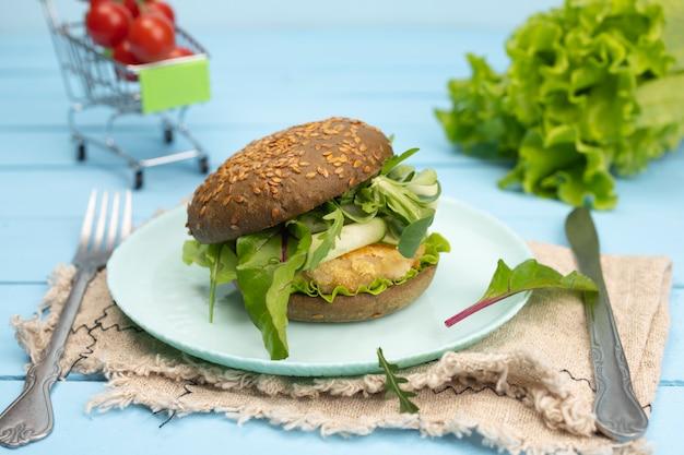 Hamburger di pesce sano con rucola su sfondo blu.