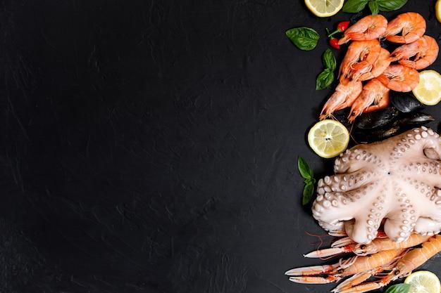 Assortimento sano di pesce e frutti di mare su sfondo nero. vista dall'alto. frutti di mare su fondo rustico nero.