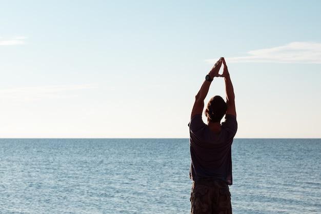Corpo sano e in forma. stile di vita attivo. uomo che esercita yoga sulla spiaggia