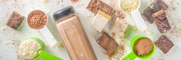 Forma sana e sfondo sportivo. concetto dimagrante. varietà di sapori di polvere di cocktail proteico, cocktail pronti in bottiglia e barre su sfondo bianco.