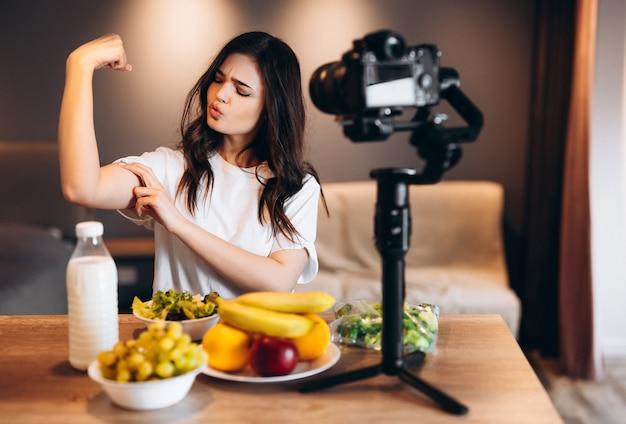 Blogger di cibo sano giovane donna che cucina fresca di frutta insalata vegana in studio di cucina che filma tutorial sulla fotocamera per il canale video l'influencer femminile mostra quanto è forte a causa della salute