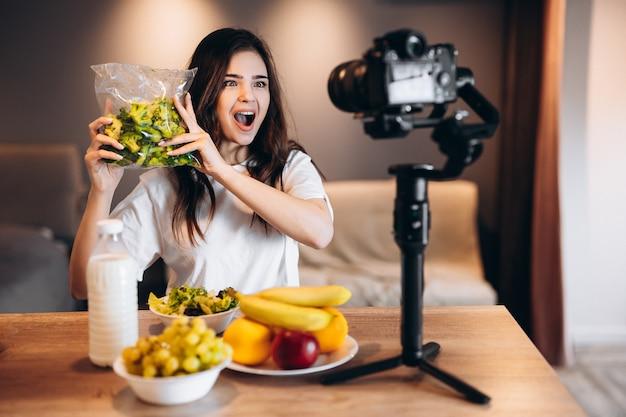 Blogger di cibo sano giovane donna che cucina fresca di frutta insalata vegana in studio di cucina che filma tutorial sulla fotocamera per canale video